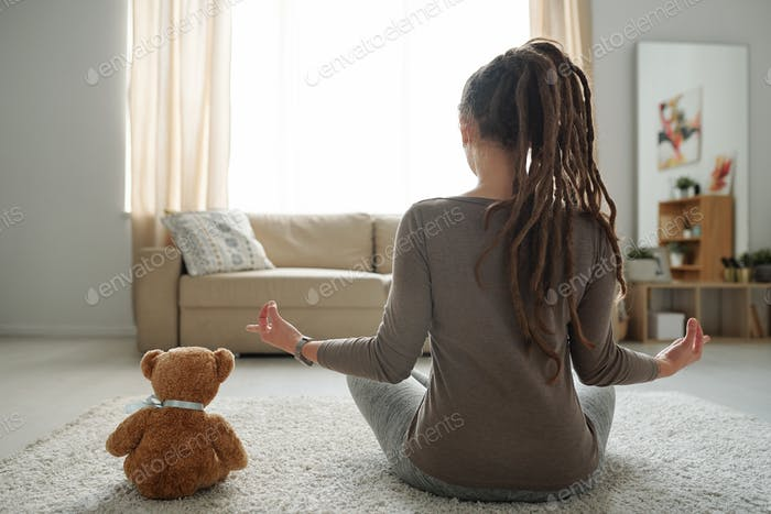 Young female sitting in pose of lotus on the floor and brown teddybear near by