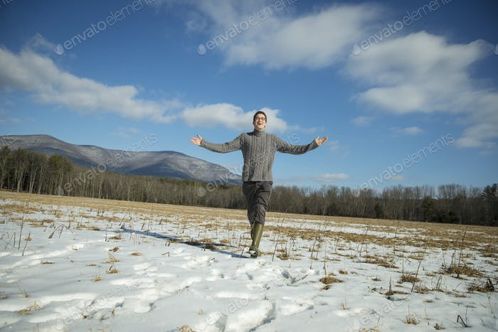 A man in a cable knit jumper and muck boots in a snowy rural landscape, arms outstretched