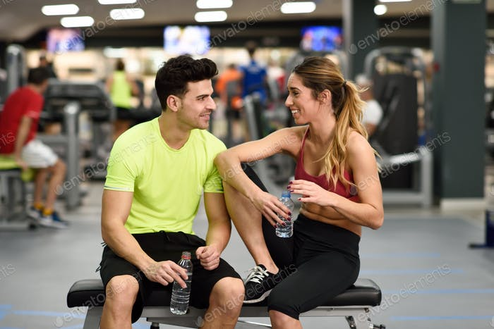 Man and woman drinking water after workout