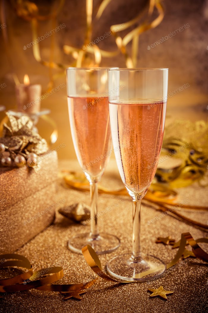 Two glasses of champagne with home decoration in golden tone for party