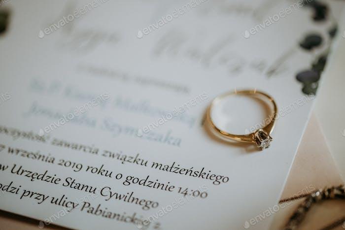 Engagement ring on wedding invitation