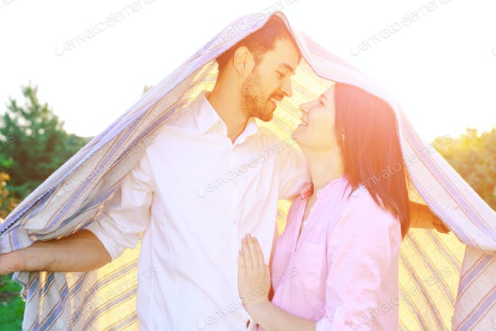 Happy couple portrait wrapped in a blanket