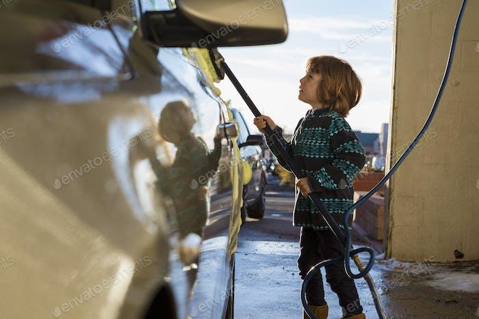 4 year old boy washing a car in car wash