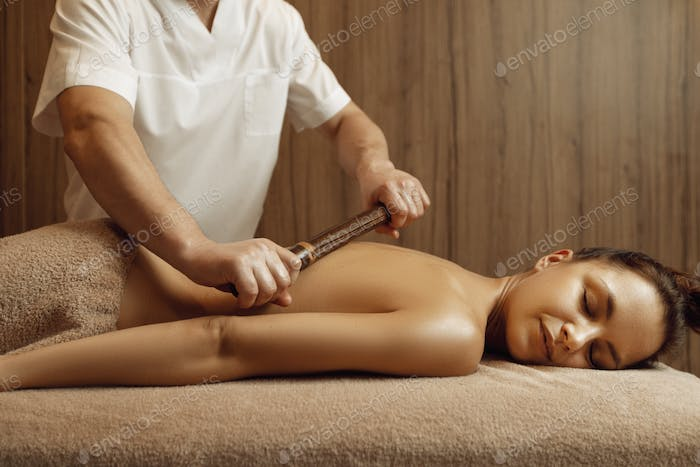 Male masseur pampering back to young woman