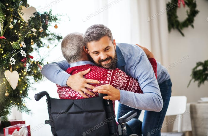 A hipster man hugging his senior father in wheelchair at Christmas time.