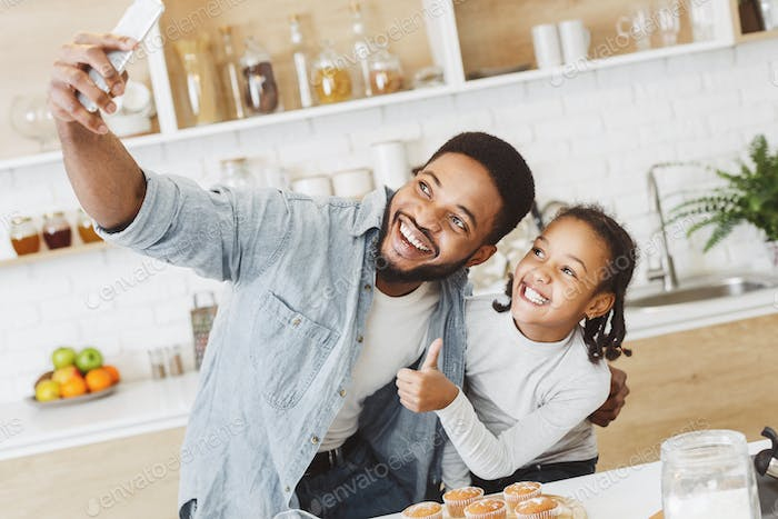 Black man and little girl making selfie in kitchen