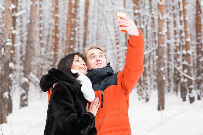paar in der Liebe lächelnd und machen selfie im Winter im freien