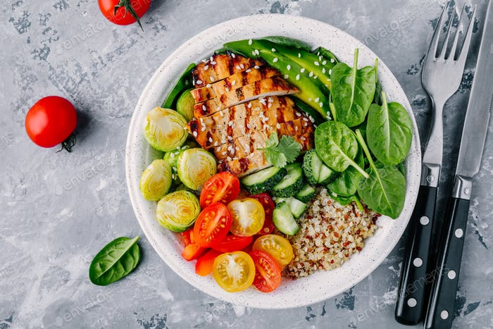 Buddha bowl with grilled chicken, quinoa, spinach, avocado, brussels sprouts, tomatoes, cucumbers