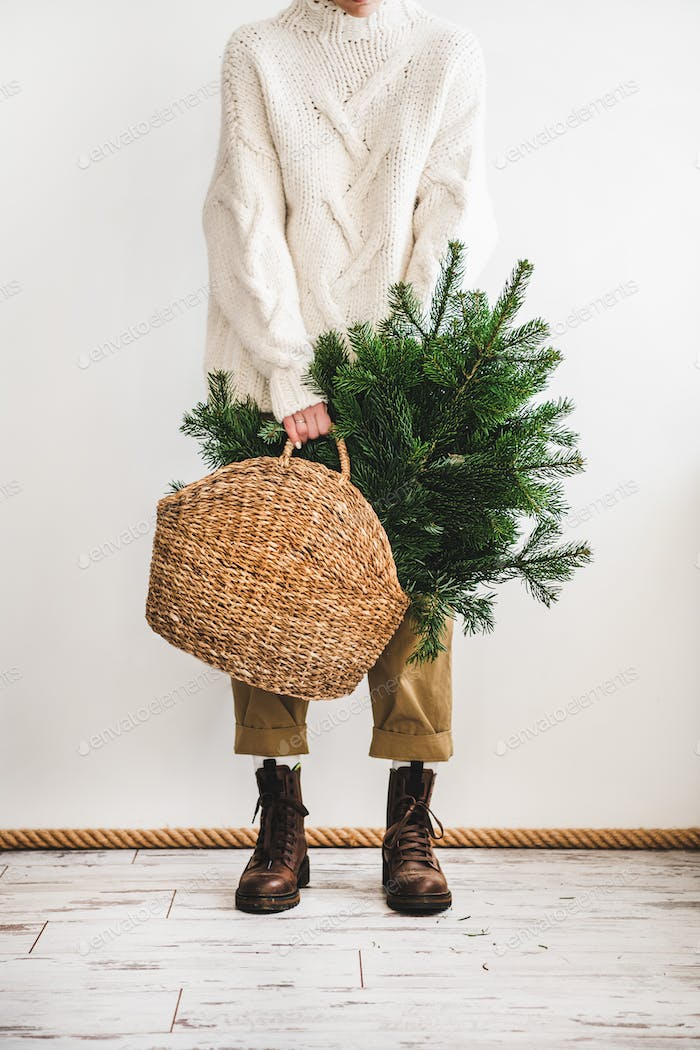 Evergreen Christmas tree branches in bag in hands of female