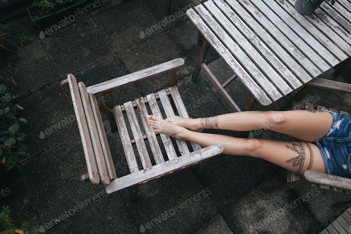 Gekürzte Aufnahme weiblicher Beine mit Tattoos auf Holzstuhl außen