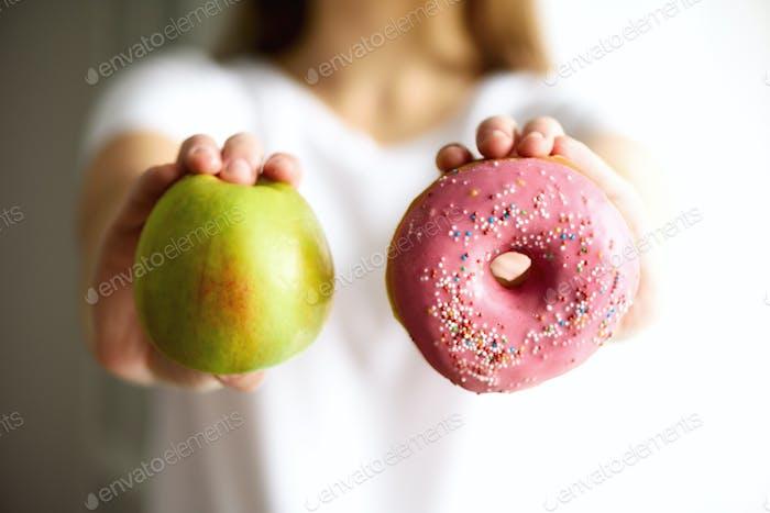 Mujer joven en camiseta blanca elegir entre manzana verde o comida chatarra, rosquilla. Desintoxicación limpia y saludable  .