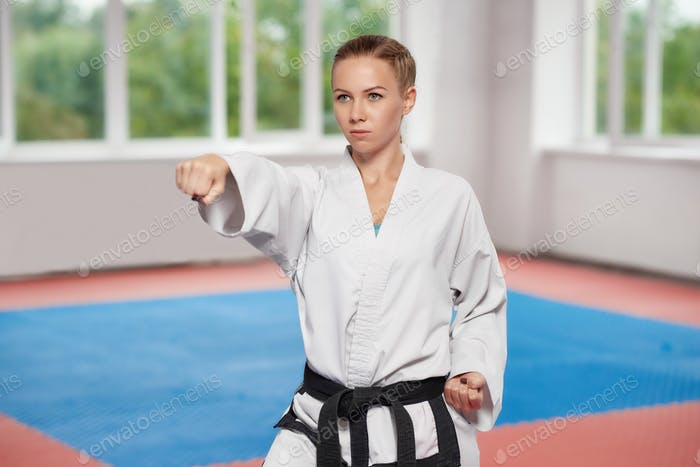 Girl wearing in white kimono with black belt standing in karate pose