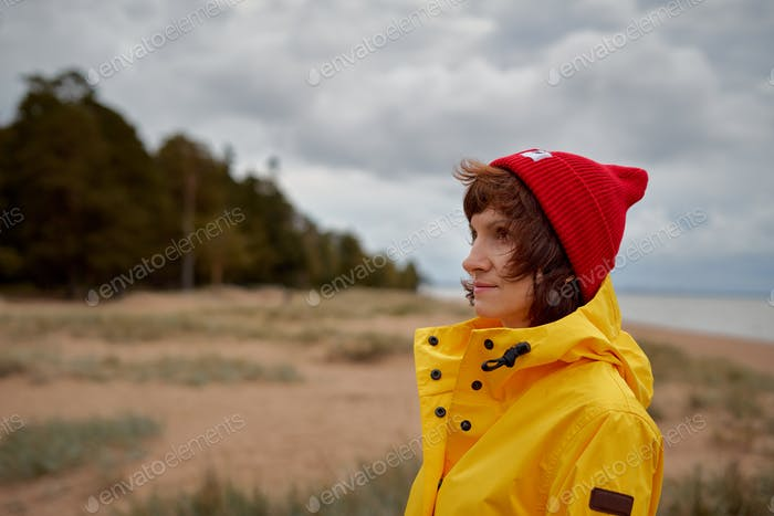 One with nature. Mature beautiful woman looking to forest in bright yellow jacket and red hat