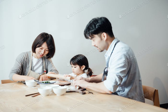 Parents teaching daughter to make dumplings at home