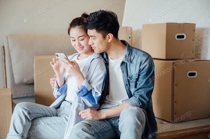 Young couple using smartphone during moving house