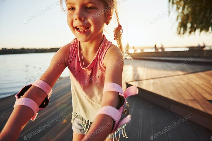 Happy cute kid riding on her roller skates. Summertime leisure and weekends