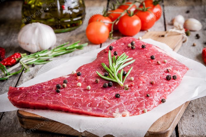 fresh raw meat steak on a cutting board with rosemary and pepper