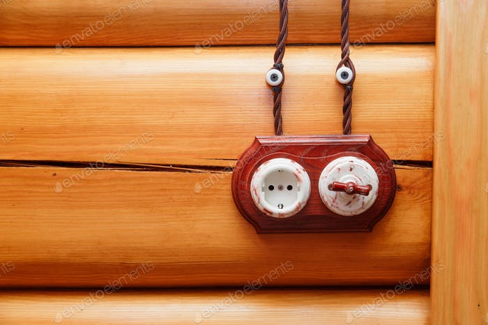 Electrical socket and switch in retro style on a wooden wall. Design of electricians in the house.