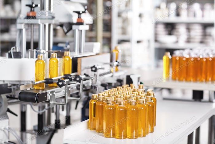 Kosmetik-Fabrik. Abfüllanlage gefüllt mit gelbem Shampoo. Automatisierter Prozess in der Fabrik. Linie von b