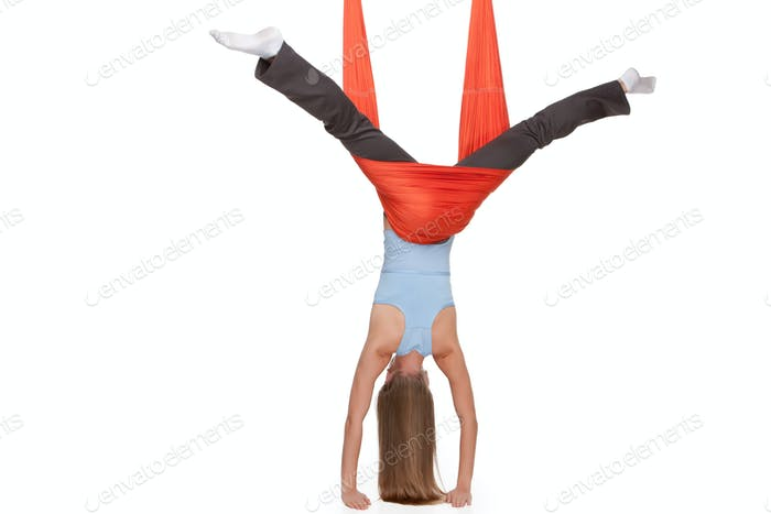Young woman making antigravity yoga exercises in stretching twine