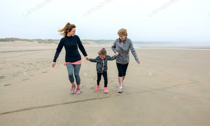 Three generations female running on the beach