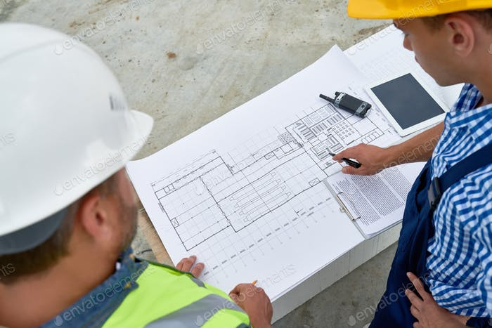 Builders Checking Blueprints on Site
