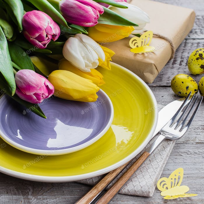 Easter table setting with spring tulips, colorful quail eggs and cutlery on shabby wooden table.