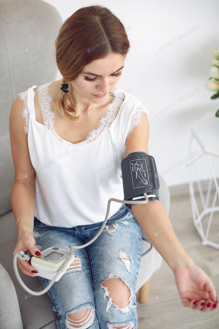 Mujer mide a sí misma la presión en casa