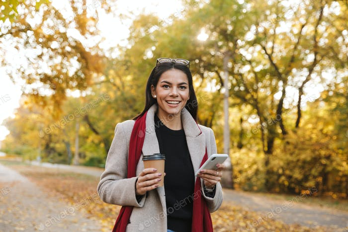 Portrait of smiling brunette woman drinking takeaway coffee and typing on cellphone in autumn park