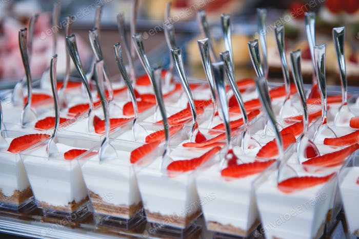 Portion cups with strawberries and cream for a buffet table.