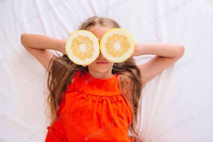 Little girl covering eyes with lemon halves near eyes