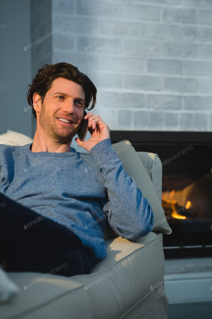 Man talking on mobile phone in living room at home