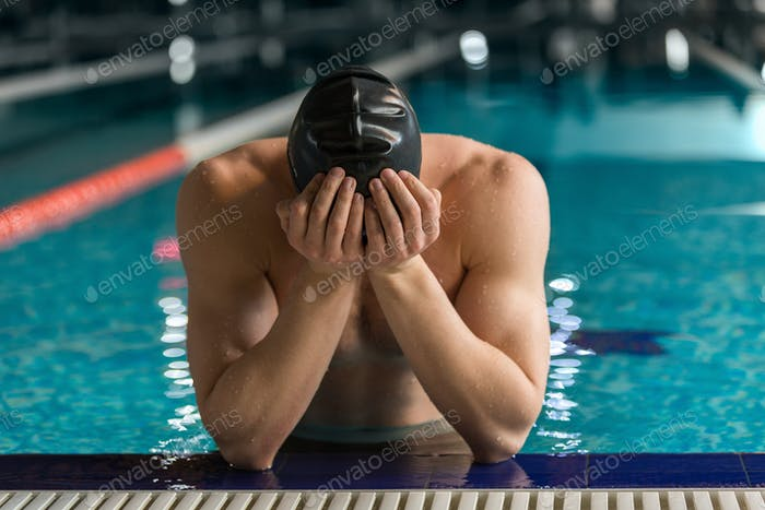Male swimmer standing at the edge of a pool