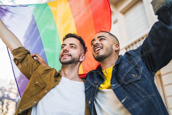 Gay couple embracing and showing their love with rainbow flag.