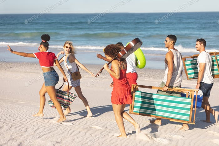 Side view of group of happy diverse friends walking together on the beach
