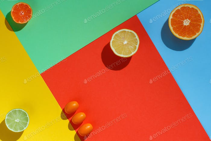 Citrus fruits on a coral red, yellow, blue and green background
