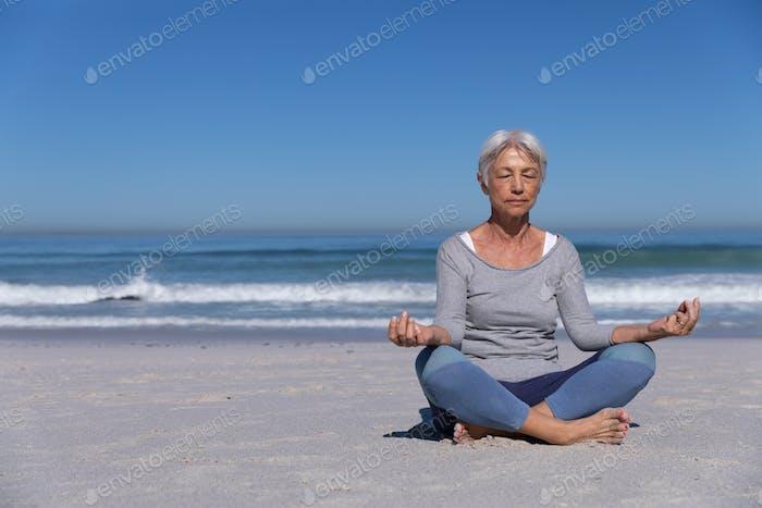 Ältere kaukasische Frau meditiert am Strand.