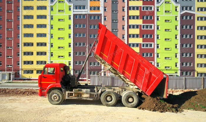 Multistorey building apartment house and dump truck unload soil.