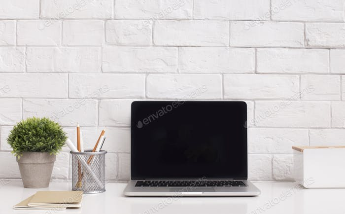 Modern laptop with blank screen and stationery on desktop