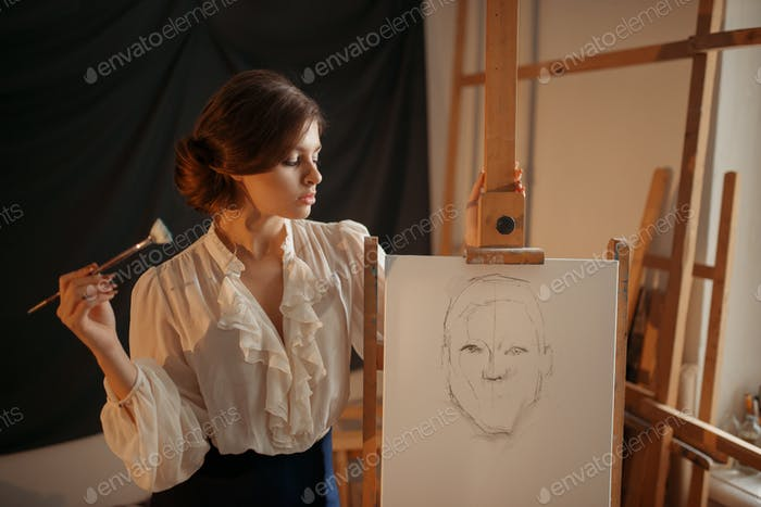 Female painter with brush standing against easel