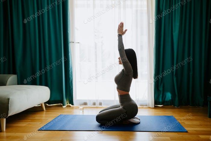 Mujer joven atractiva practicando yoga en casa. práctica de estiramiento