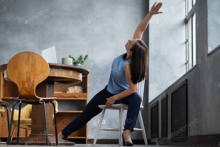 Woman practicing yoga using chair, stretching in Extended Side Angle exercise