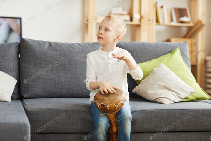 Caucasian boy playing djembe