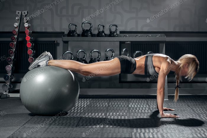 fit blonde female doing exercise with fit ball