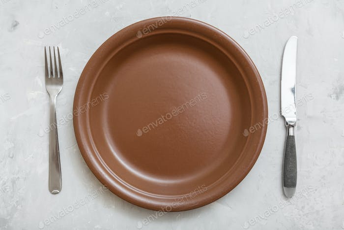top view brown plate with knife, spoon on concrete