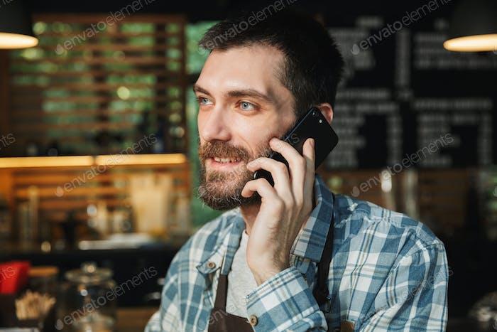 Porträt der glücklich barista Kerl im Gespräch auf Handy in Straße caf