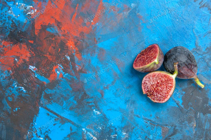 Top view of split and full fresh black mission figs on the left side on blue background