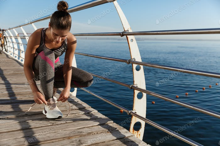 Outdoor shot of attractive sportswoman tying shoelaces on a pier, jogging at seaside