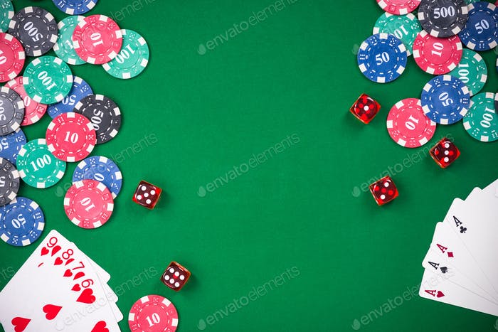 Casino games related items on green table, copy space