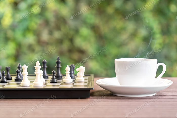 Coffee cup on wood table with Chess board